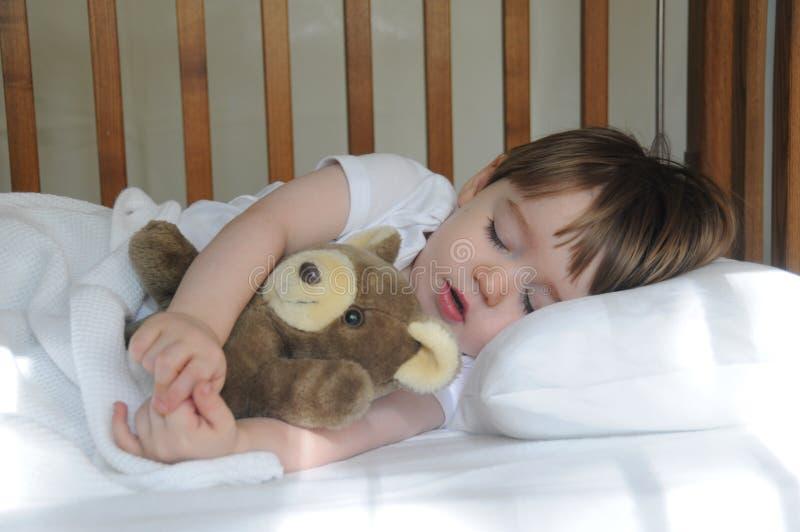 Weinig jongensslaap met teddybeer stock foto