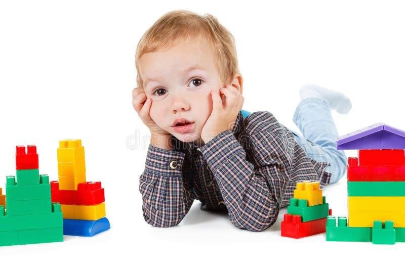 Weinig jongensspel met stuk speelgoed en bouwt geïsoleerd huis op wit stock foto's