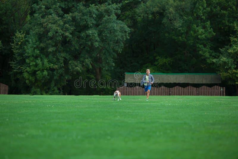 Weinig jongenstiener met zijn hondbuldog in park op een zonnige dag op het groene land van het graspark geniet van het leven same stock foto