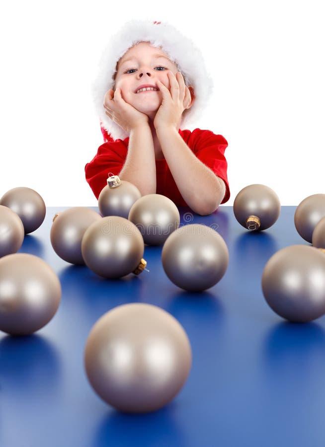 Weinig jongenszitting achter de ornamenten van Kerstmis stock afbeelding
