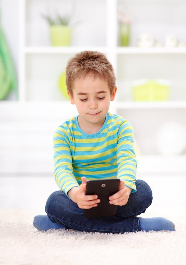 Weinig jongenszitting en lezing van tablet royalty-vrije stock afbeelding