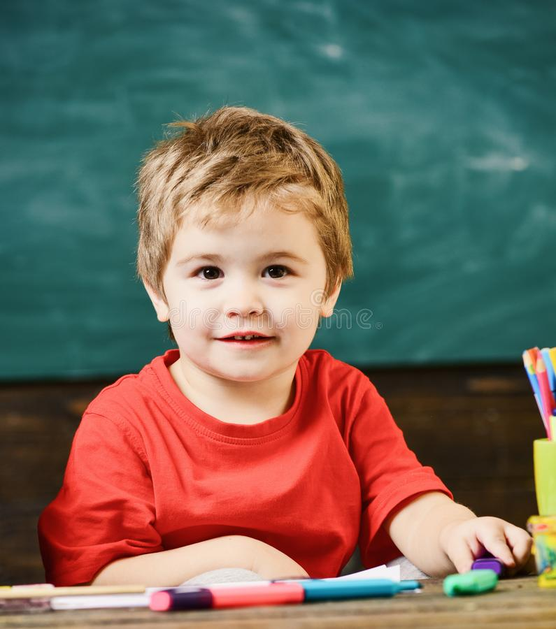 Weinig jongenszitting in het klaslokaal Blond leuk jong geitje die purpere teller houden royalty-vrije stock fotografie