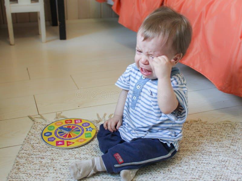 Weinig jongenszitting op de vloer, hij verstoorde en ` s die schreeuwen Chil stock afbeelding