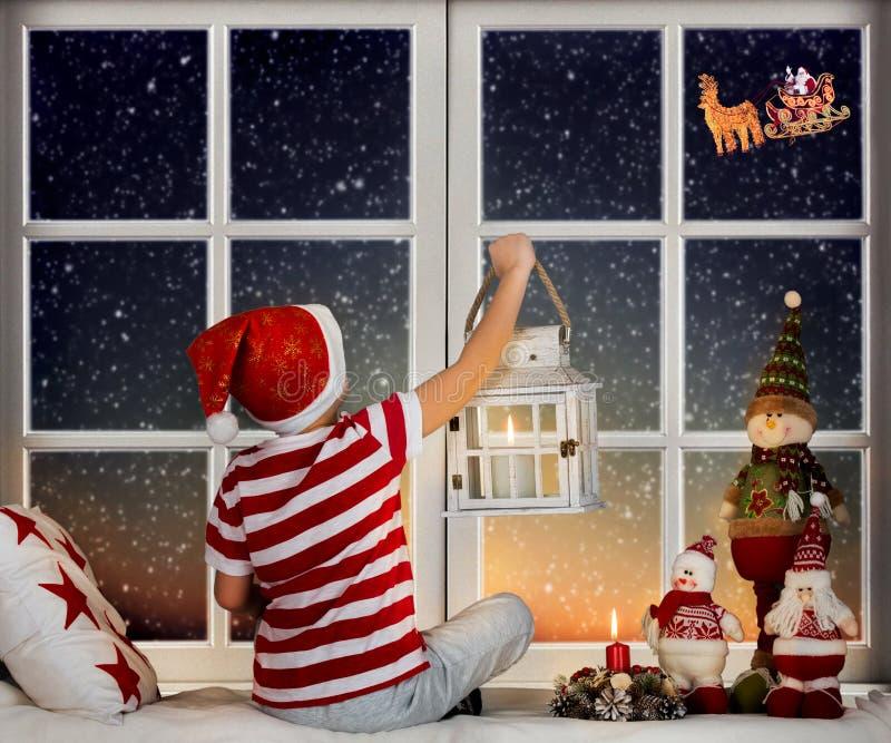 Weinig jongenszitting op het venster en het bekijken in Santa Claus die in zijn ar tegen maanhemel vliegen stock fotografie