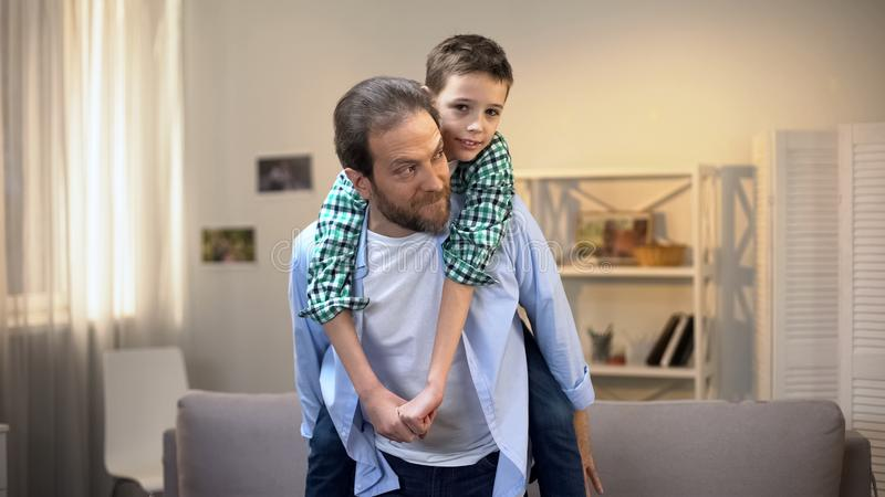 Weinig jongenszitting op rug van zijn vader, mannelijke familieleden die pret hebben stock fotografie