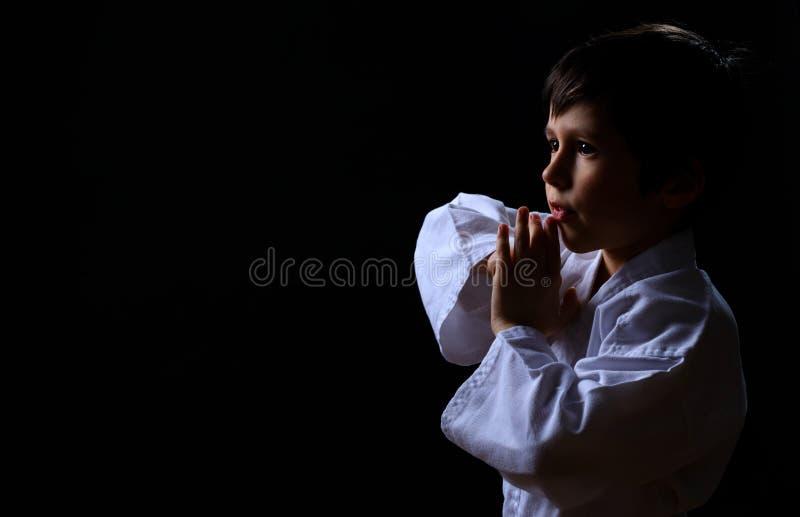 Weinig karatejong geitje in witte kimono die op donkere achtergrond wordt geïsoleerd Portret van jongen klaar voor vechtsportenst stock afbeelding