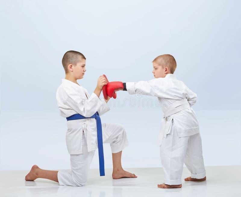 Weinig karateka slaat stempel op de simulator die de broer houdt stock fotografie