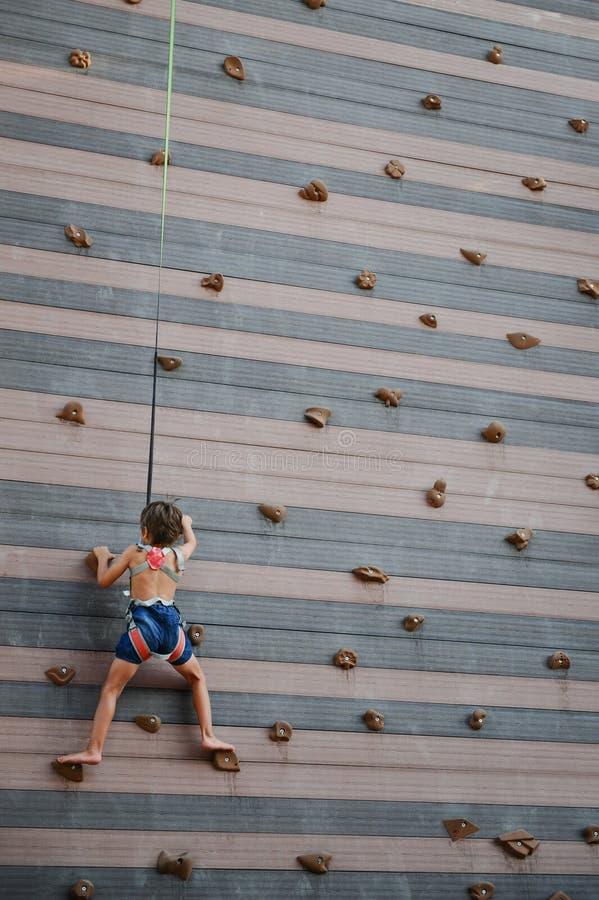 Weinig Kaukasisch gezond jong geitje die rotsmuur in openlucht beklimmen royalty-vrije stock fotografie