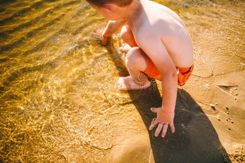 Weinig Kaukasisch jongenskind zit dichtbij een rivier op een zandig strand en raakt de oppervlakte van het water met zijn handen  stock afbeelding