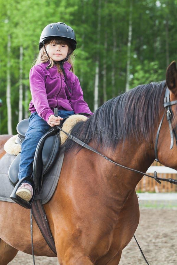 Weinig Kaukasisch meisje berijdt een paard stock foto