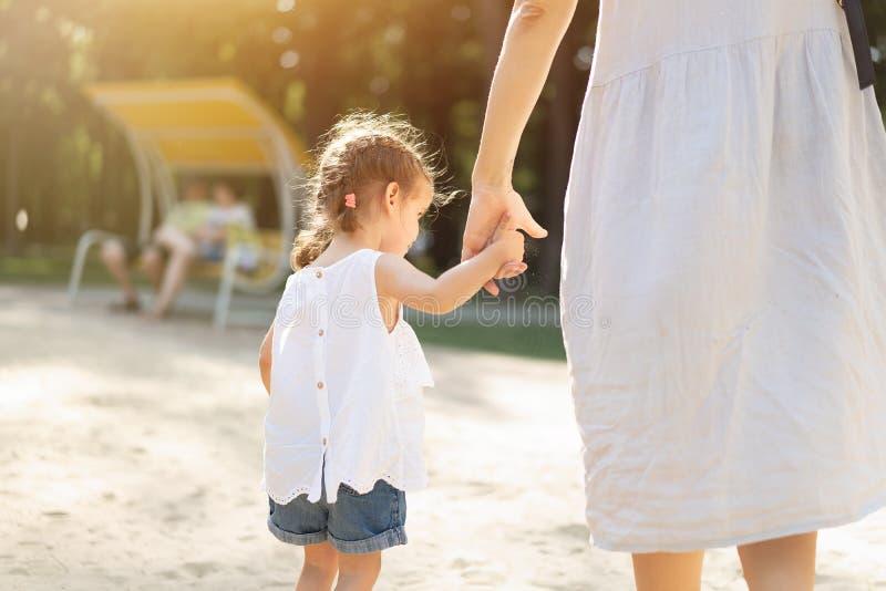 Weinig Kaukasisch meisje die haar moeder houden door de hand voor een gang in een de zomerpark Sterke familie en liefde van kinde stock foto