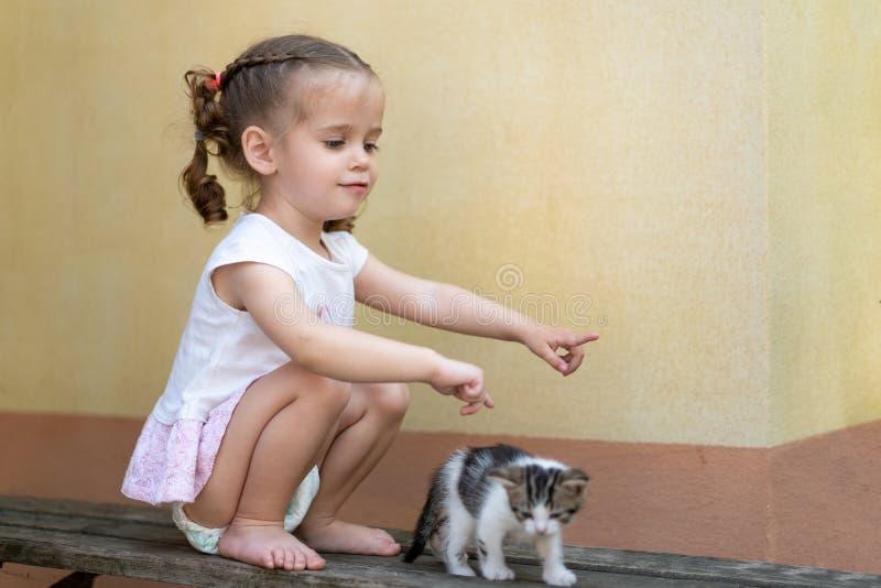 Weinig Kaukasisch meisje die op een de zomerdag spelen met een klein katje stock foto's
