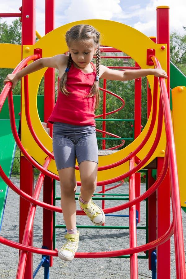 Weinig Kaukasisch meisje die op speelplaats spelen, die onderaan de treden komen royalty-vrije stock fotografie