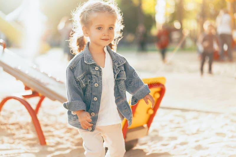 Weinig Kaukasisch meisje gekleed in een denimjasje wordt gespeeld op de speelplaats op een heldere zonnige dag royalty-vrije stock afbeelding