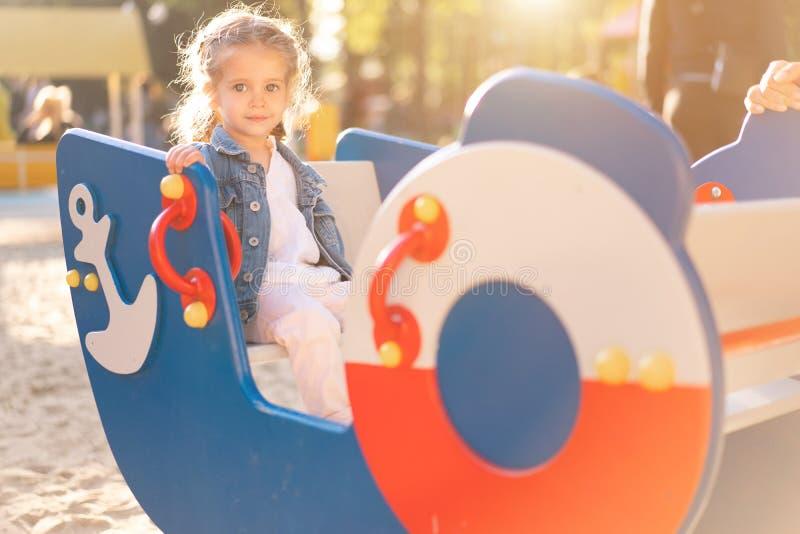 Weinig Kaukasisch meisje gekleed in een denimjasje wordt gespeeld op de speelplaats op een heldere zonnige dag stock afbeelding