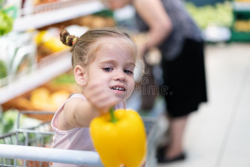Weinig Kaukasisch meisje kiest verse groenten in de supermarkt stock fotografie