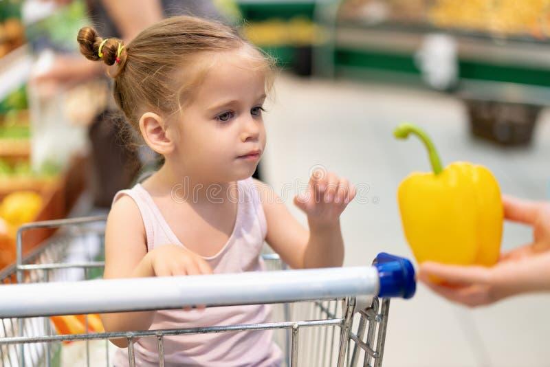 Weinig Kaukasisch meisje kiest verse groenten in de supermarkt stock afbeelding