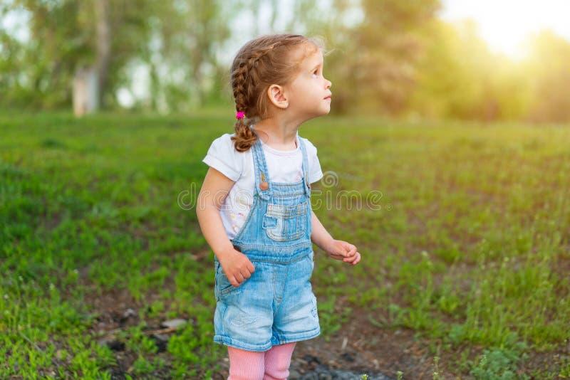 Weinig Kaukasisch meisje loopt op aard gekleed in denimoverall stock afbeeldingen