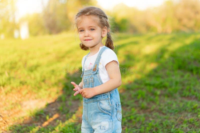 Weinig Kaukasisch meisje loopt op aard gekleed in denimoverall stock foto