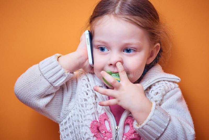 Weinig Kaukasisch meisje met een telefoon in haar hand op een gekleurde achtergrond, een plaats voor tekst stock foto's