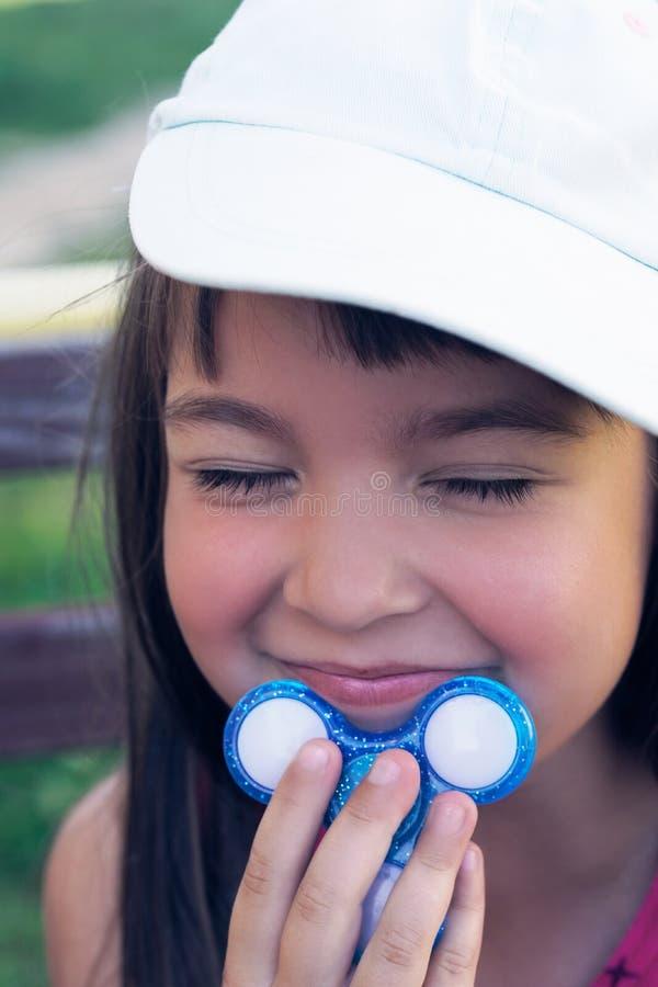 Weinig Kaukasisch meisje in wit GLB houdt een spinner door de kin en glimlacht openlucht stock afbeeldingen