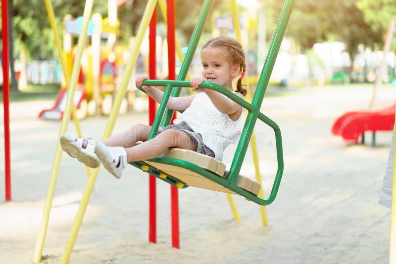 Weinig Kaukasisch meisjeskind die op een schommeling op de speelplaats op een zonnige de zomerdag berijden royalty-vrije stock fotografie