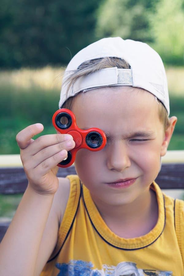 Weinig Kaukasische die jongen met Fidget Spinner aan zijn ogen in openlucht wordt gesteund stock foto's