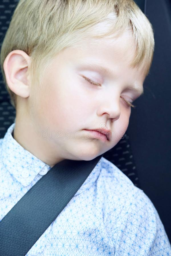 Weinig Kaukasische jongen die in de zetel van de autoveiligheid sleepping stock afbeelding