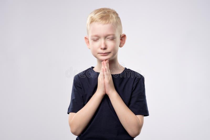 Weinig Kaukasische jongen met het blonde haar bidden stock afbeelding