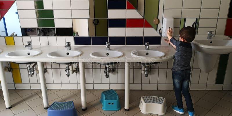 Weinig Kaukasische jongen wast zijn handen zelf in het toilet van kinderen in kleuterschool, die zich met van hem terug naar de c royalty-vrije stock afbeelding