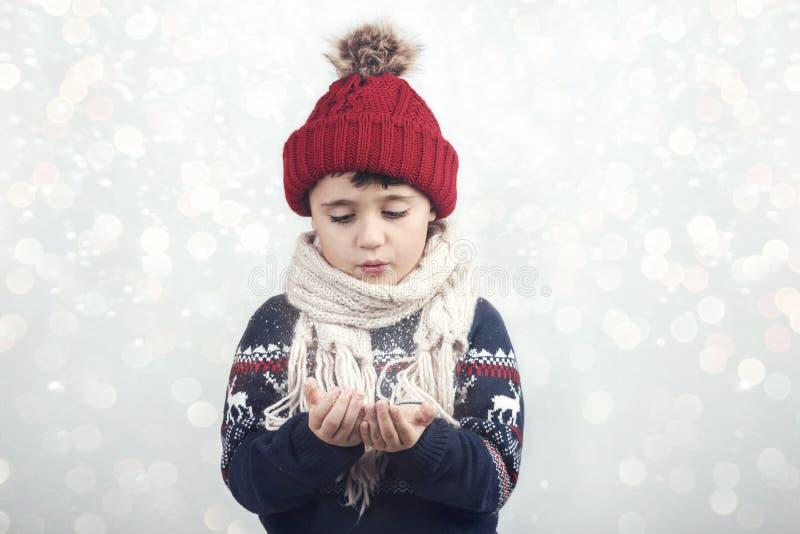 Weinig kind blaast sneeuw stock afbeeldingen