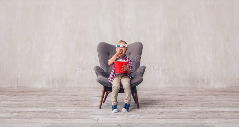 Weinig kind die in 3d glazen popcorn eten royalty-vrije stock afbeelding