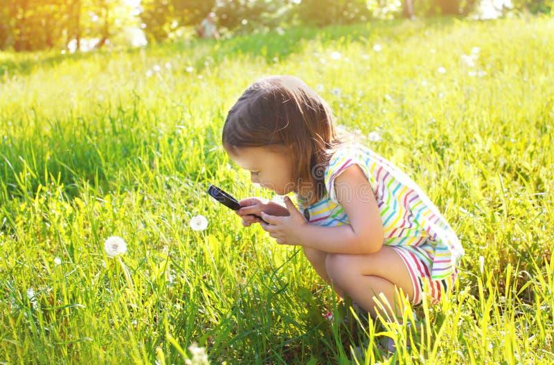 Weinig kind die door een vergrootglas op paardebloem kijken stock foto