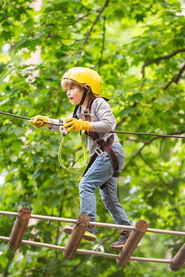 Weinig kind die in het park van de avonturenactiviteit met helm en veiligheidsmateriaal beklimmen Klimmerkind bij de opleiding Ka stock foto