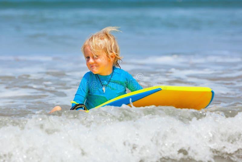 Weinig kind die met bodyboard op de overzeese golven zwemmen stock afbeelding