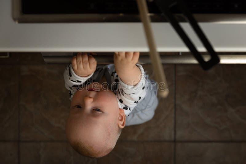 Weinig kind die met elektrisch fornuis in de keuken spelen terwijl het zitten in highchair Babyveiligheid in keuken stock afbeeldingen