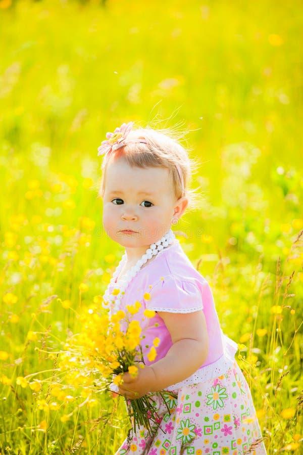 Weinig kind die met gebied spelen bloeit op de lente of de zomerdag stock afbeeldingen