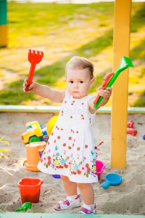 Weinig kind die met speelgoed in zand op kinderenspeelplaats spelen royalty-vrije stock fotografie
