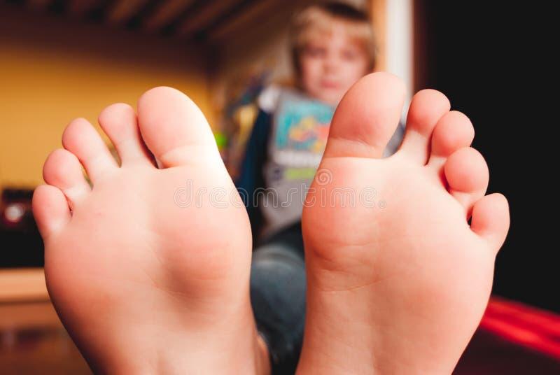 Weinig kind die op de houten vloer van zijn slaapkamer blootvoetse sensorische verbindingen liggen royalty-vrije stock afbeeldingen