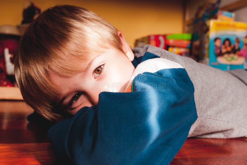 Weinig kind die op de houten vloer van zijn slaapkamer sensorische verbindingen liggen royalty-vrije stock fotografie