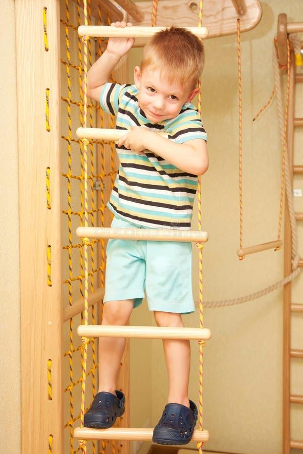 Weinig kind die op touwladder beklimmen. stock foto