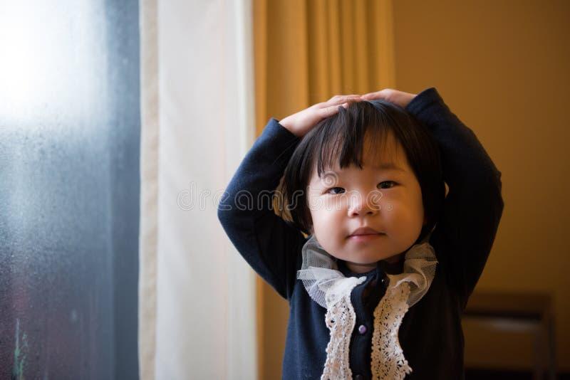 Weinig kind die zich door venster bevinden stock fotografie