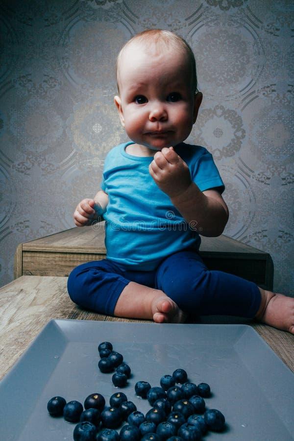 Weinig kind eet bosbessen zittend op een lijst, groot, liggen de verse bosbessen op een grijze plaat, close-up stock fotografie