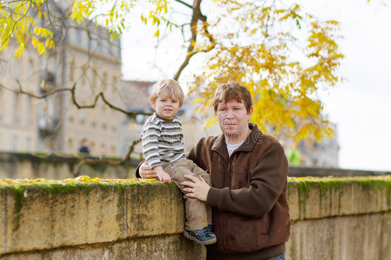 Weinig kind en jonge vader in de herfststad royalty-vrije stock foto