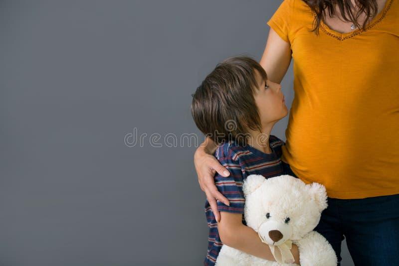 Weinig kind, jongen, die zijn zwangere geïsoleerde moeder koesteren thuis, royalty-vrije stock afbeelding