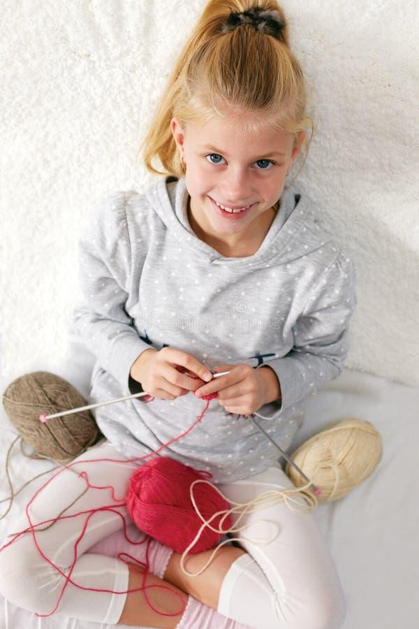 Weinig kind leert te breien stock foto