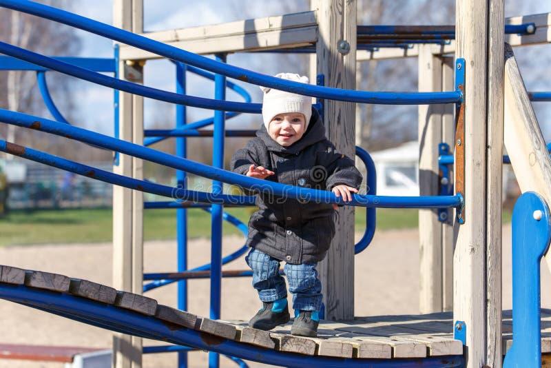 Weinig kind loopt langs de raad op de speelplaats royalty-vrije stock afbeelding