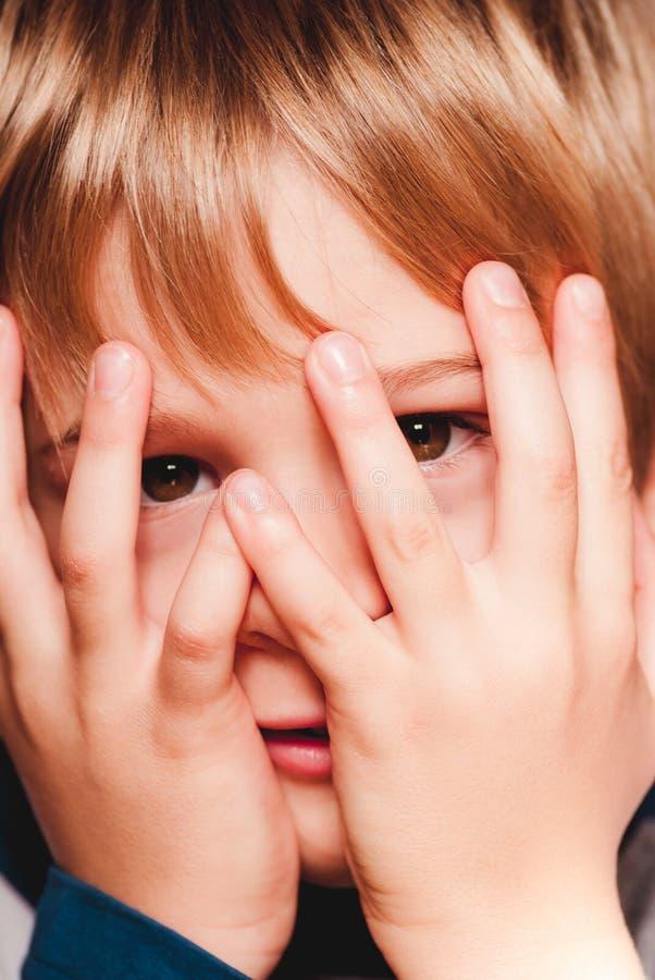 Weinig kind met handen op de gezichts sensorische verbindingen stock afbeeldingen
