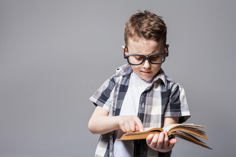 Weinig kind met schooltas en boek in studio stock fotografie