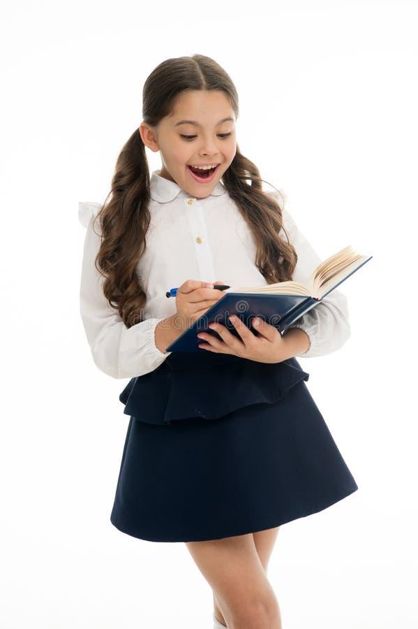Weinig kind met verrast kijkt geïsoleerd op wit Schoolmeisje met het lange boek van de haargreep met pen meisje in eenvormige sch royalty-vrije stock afbeelding
